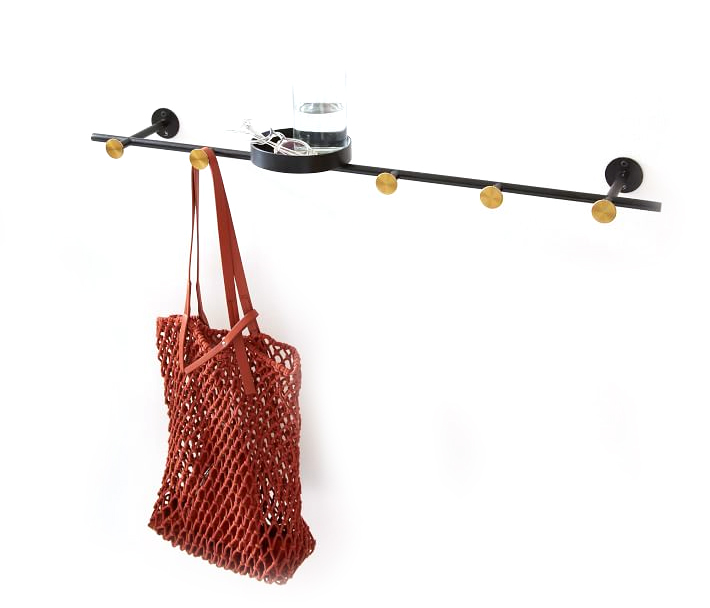 A horizontal wall-mounted coat rack with a purse hanging from it.